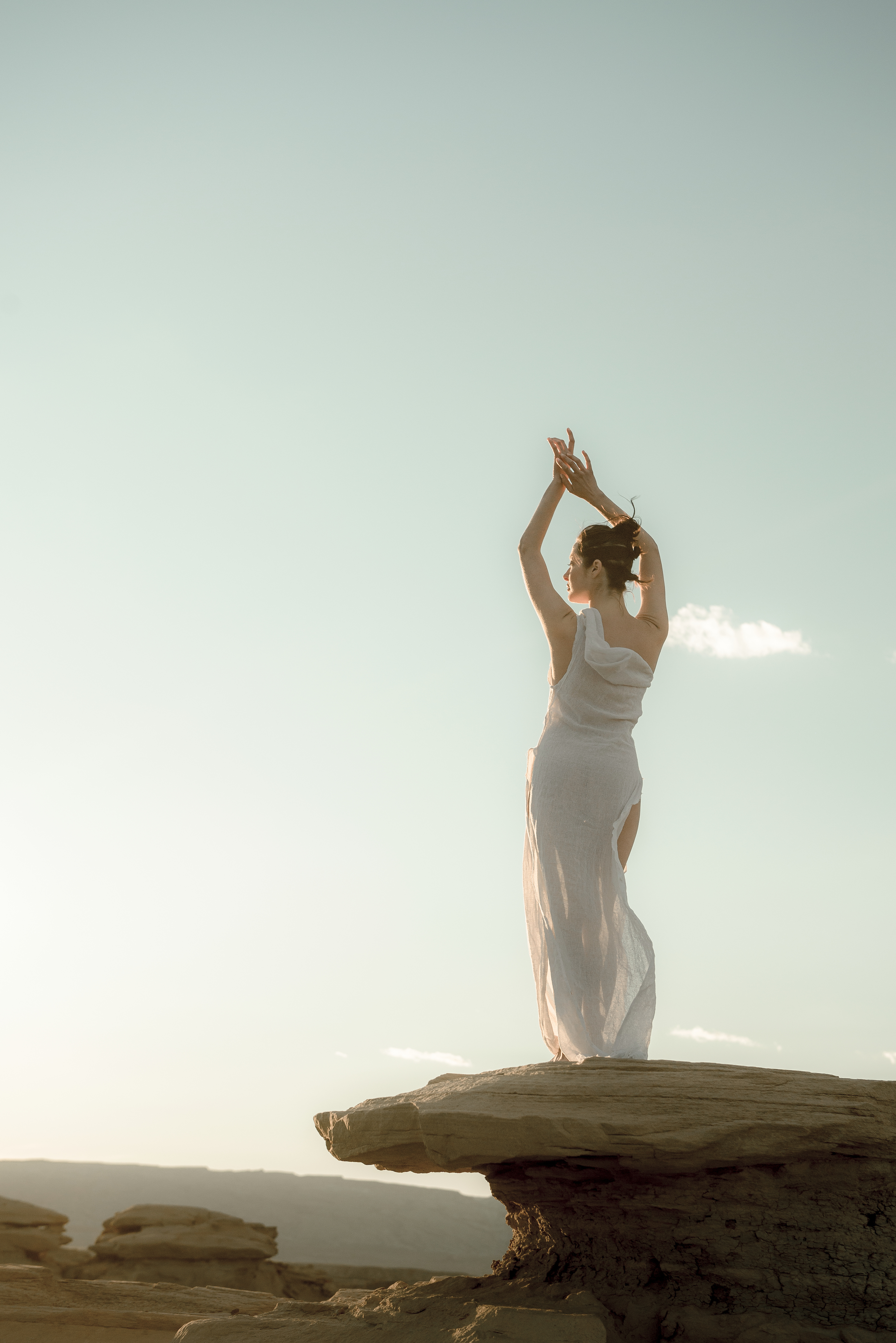 A woman holds her hands above her head while wearing a white dress at sunset