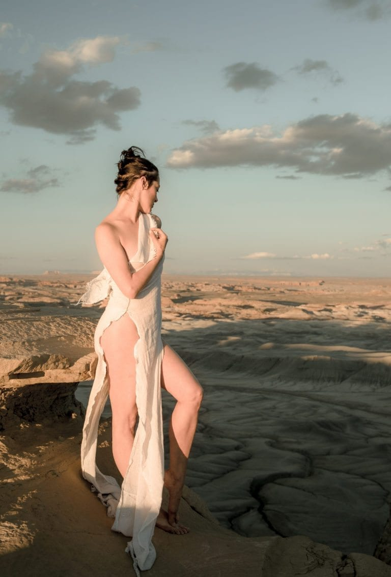 A woman peers down at a moon-like landscape while wearing a revealing dress