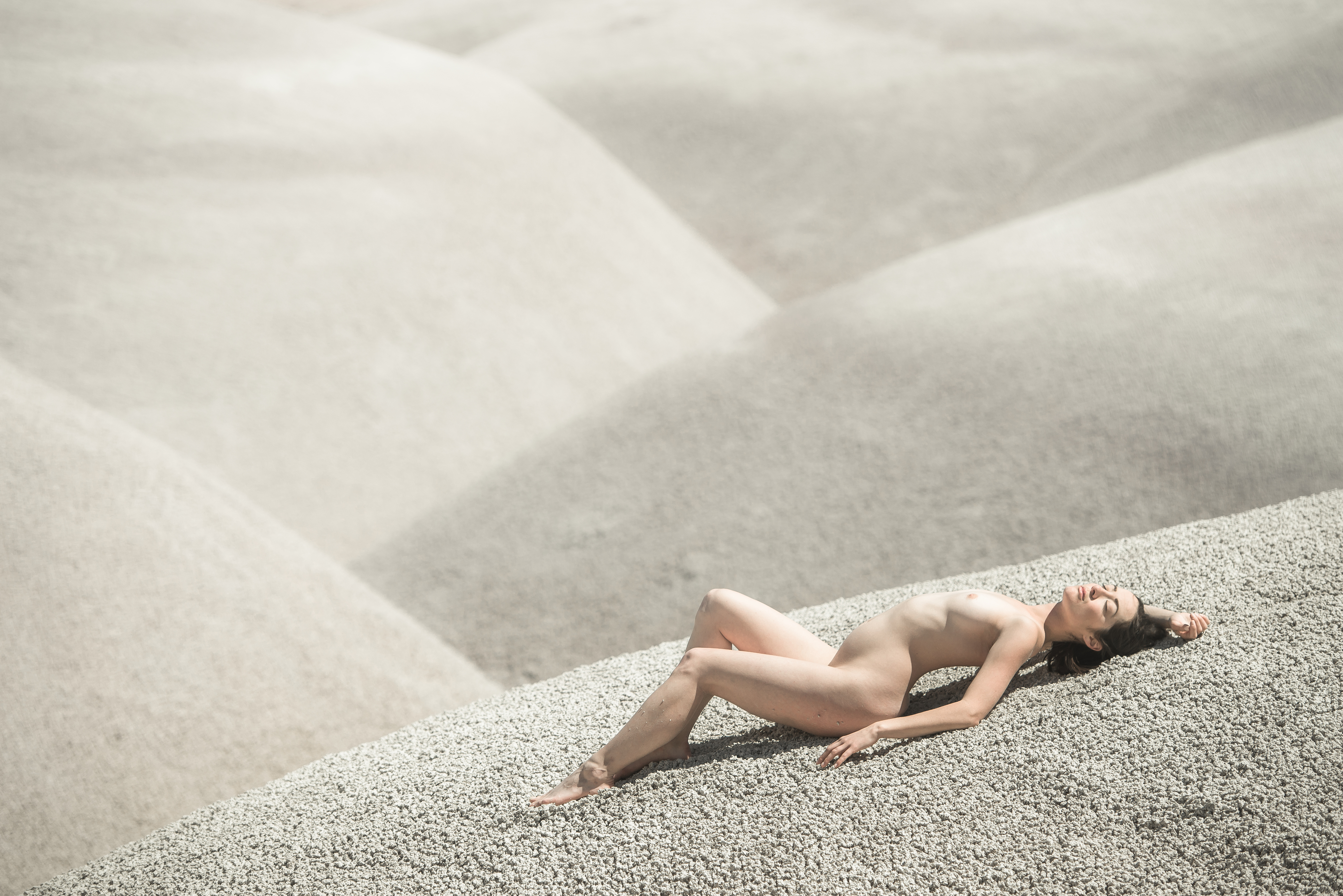 A woman lies nude on white sand dunes in southern Utah