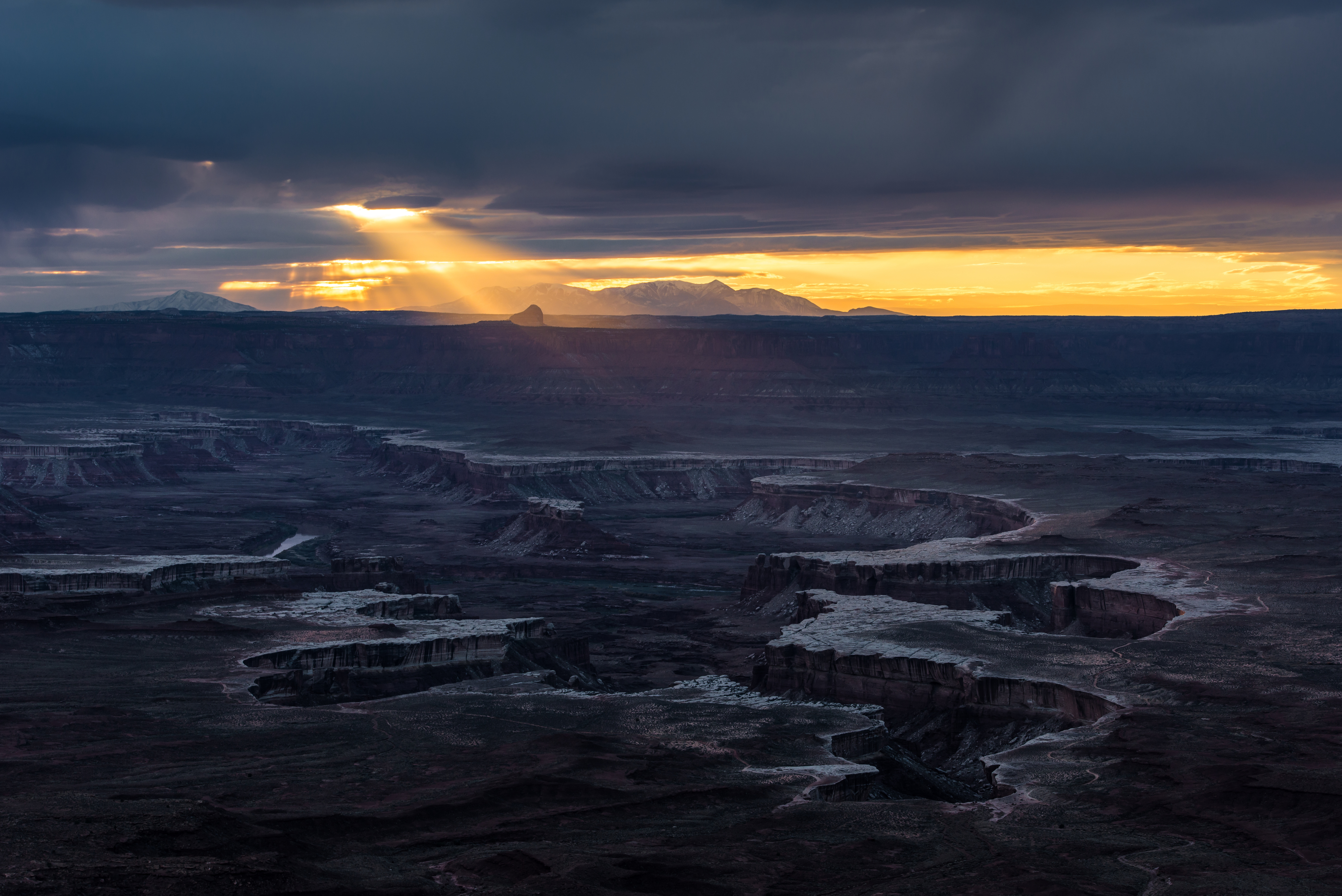 Sun beam comes through clouds over the White Rim Trail in Canyonlands National Park, Utah