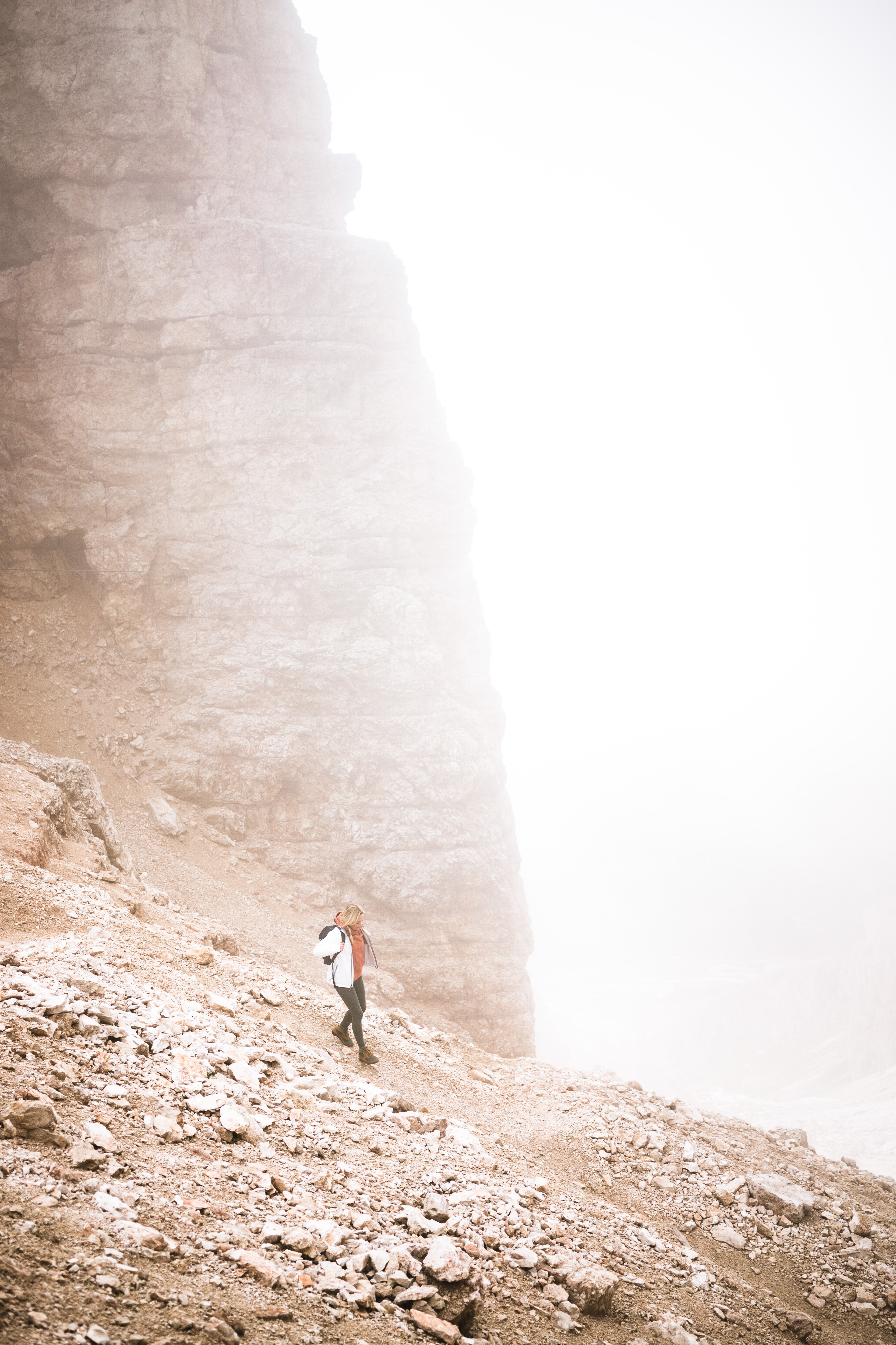 A woman hikes through a cloud in the Dolomites in northern Italy