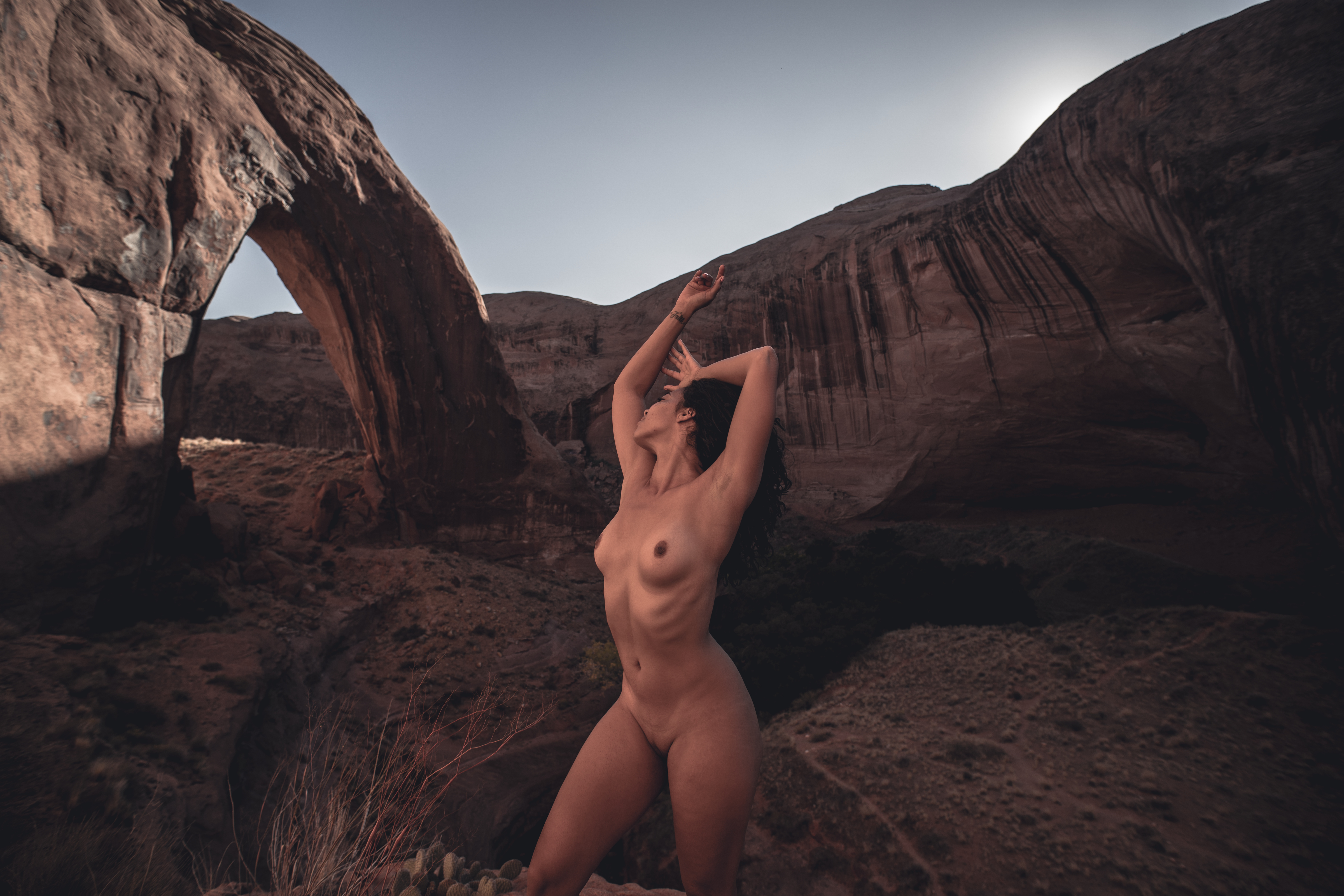 A nude black woman stretches tall with Broken Bow Arch in the background for fashion nude photographer Dylan H Brown's Impermanence series