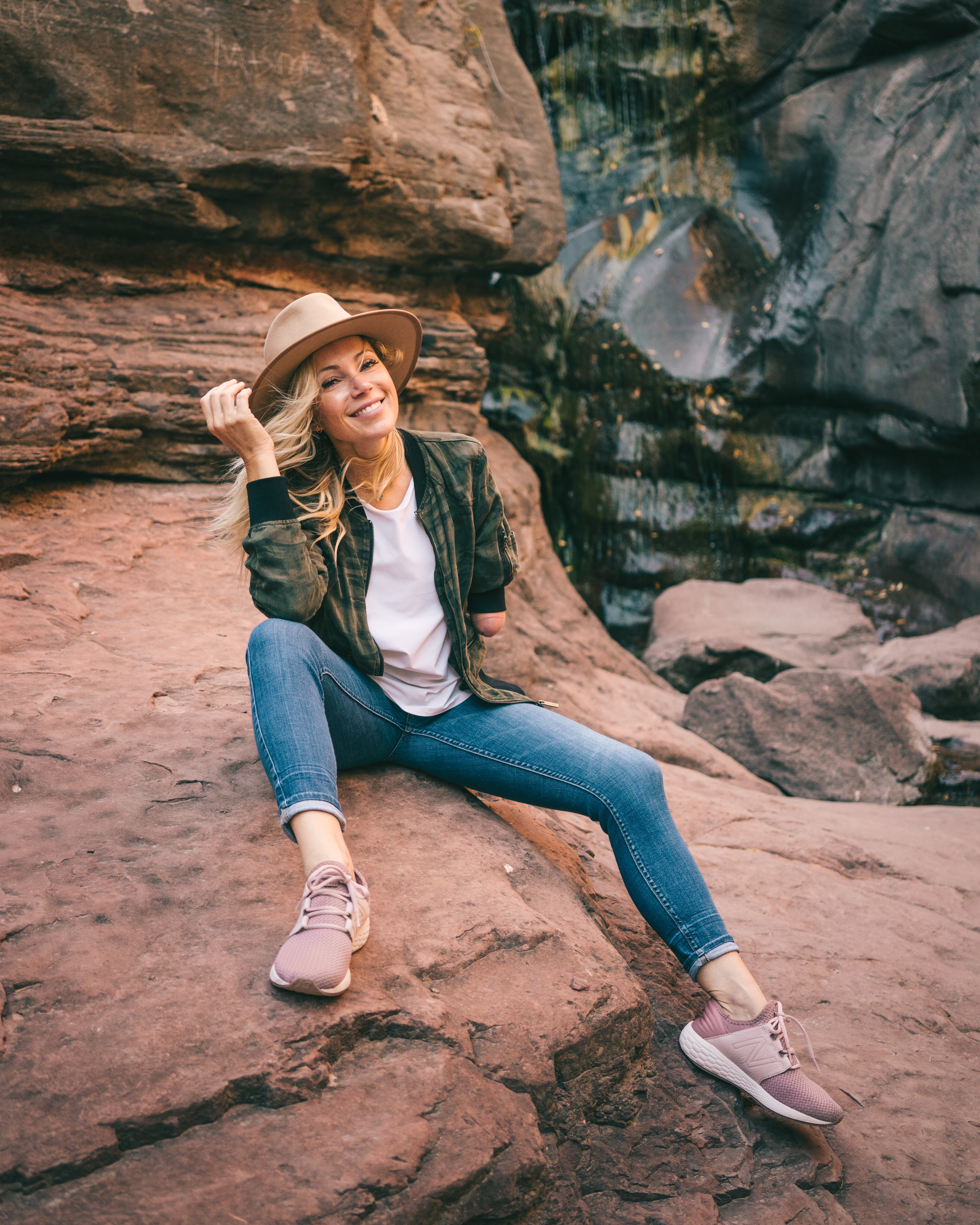 Beautiful woman sits near waterfall in trendy outfit.