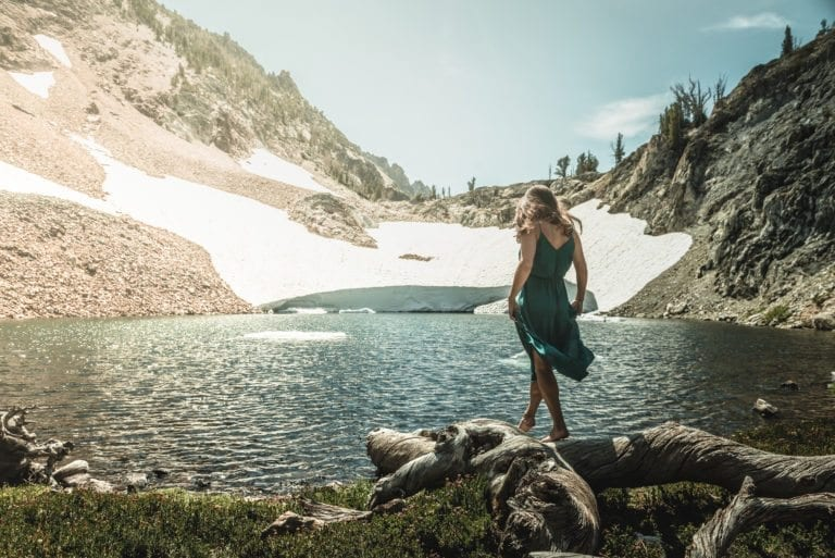 A woman in a green dress walks along a log with a high-alpine lake in the background