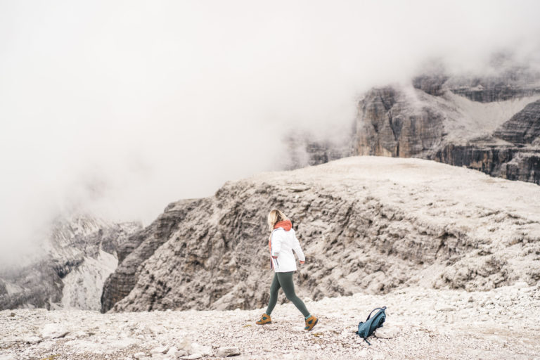A woman drops her bag to explore the cliff edge in the clouds in Northern Italy.